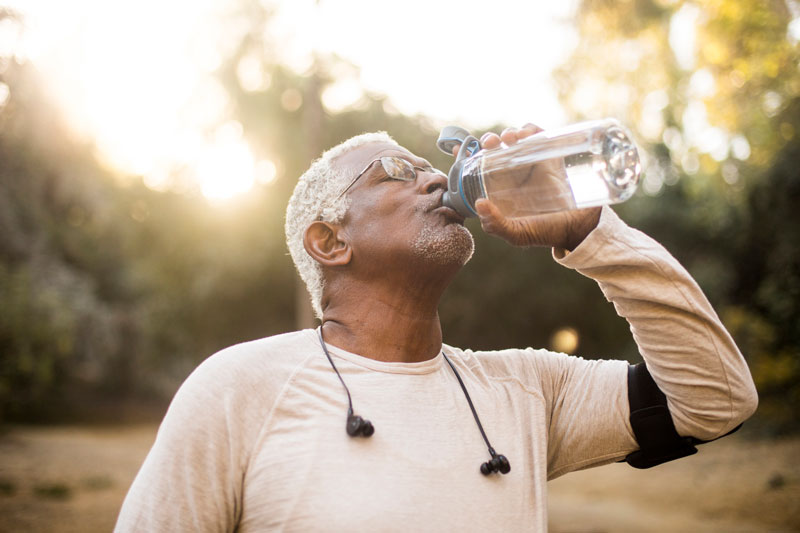 A senior African American Man drinking water after a workout