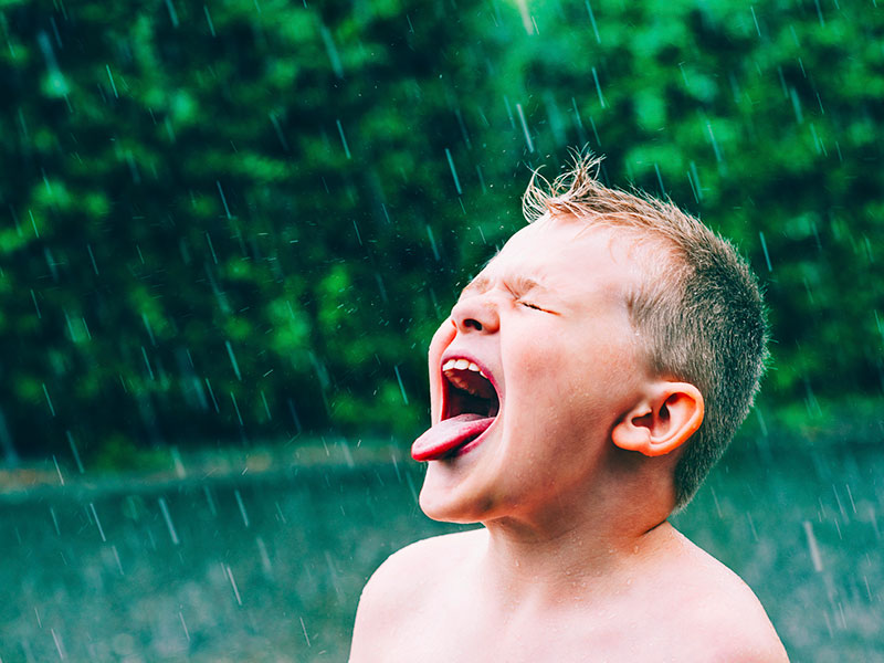 Boy sticking out his tongue to taste falling rain water