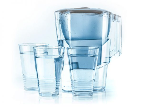 Water filter pitcher with filled water glasses on white background