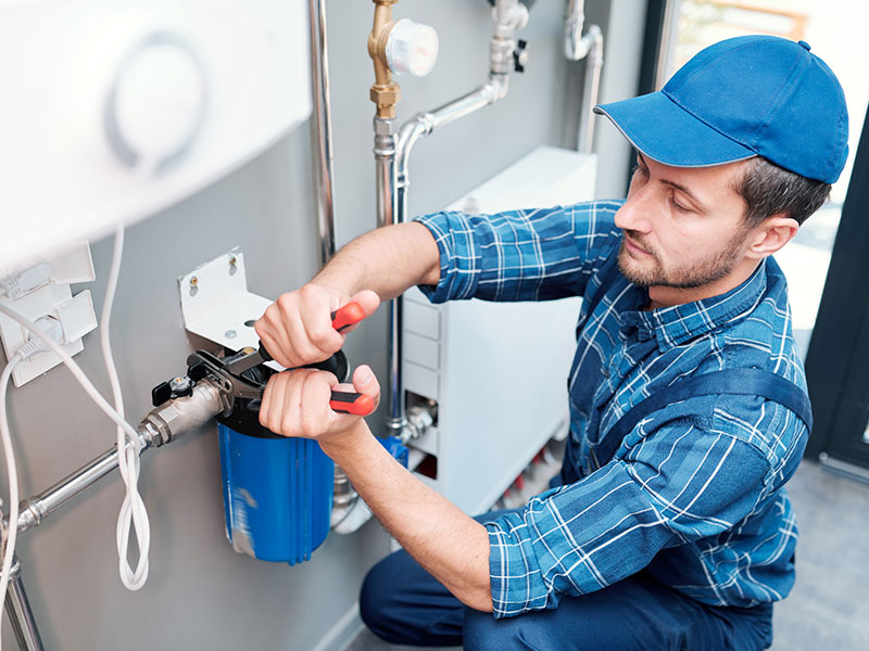 Young man in workwear using pliers while installing water filtration system