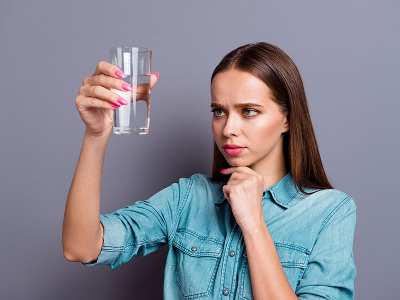 woman contemplating drinking water