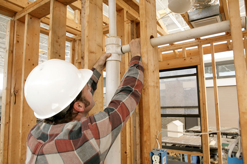 worker installing PVC water pipes