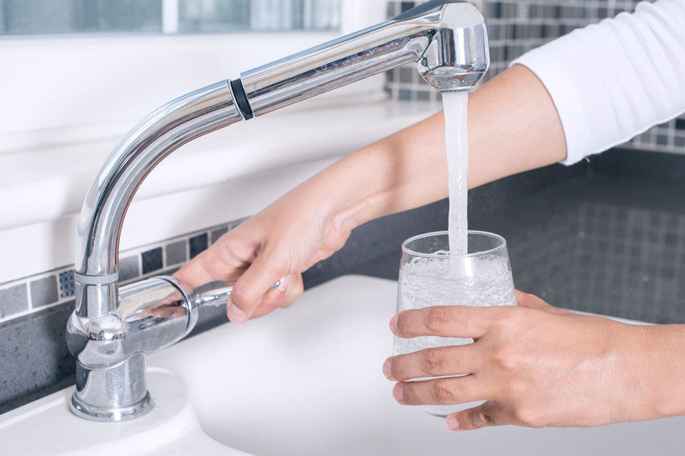 Woman filling glass of water at kitchen sink.
