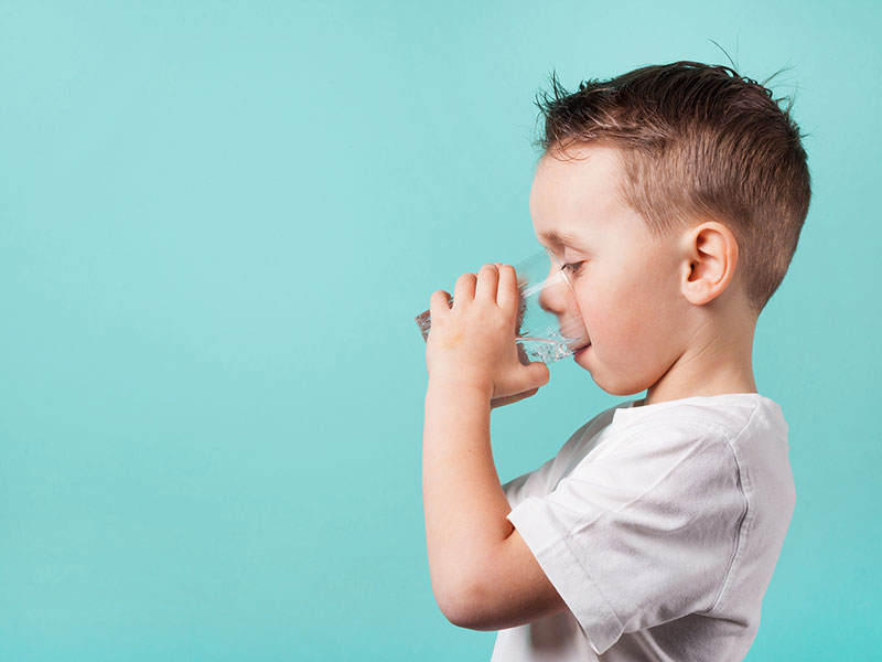 boy drinking water in front of green background