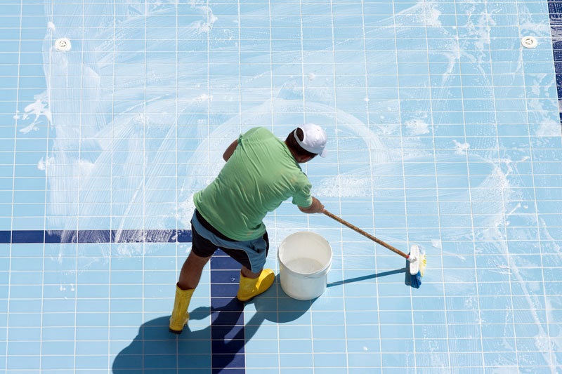 Man cleaning the tiled floor of swimming-pool