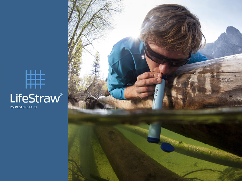 Man drinking from stream with LifeStraw